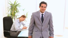 Businessman posing. While his colleague is working in background stock video footage