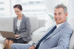 Businessman posing while his colleague working on her laptop Royalty Free Stock Image