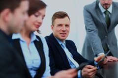 Businessman posing in the meeting room while colleagues are working behind. Royalty Free Stock Photos