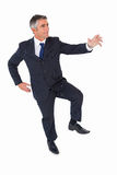Businessman posing with one foot on floor and arms out Royalty Free Stock Images