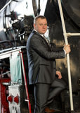 Businessman posing on stairs of old locomotive Stock Images