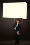 Businessman with post-it paper. Young businessman holding a big, white post-it paper Stock Images