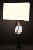 Businessman with post-it paper. Young businessman holding a big, white post-it paper Royalty Free Stock Photography