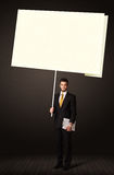 Businessman with post-it paper. Young businessman holding a big, white post-it paper Stock Photos