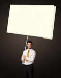 Businessman with post-it paper. Young businessman holding a big, white post-it paper Royalty Free Stock Images
