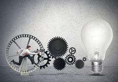 Businessman powering an idea. With gear system Royalty Free Stock Photography