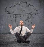 Businessman practice yoga under a rainy cloud Royalty Free Stock Photos