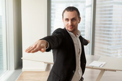 Businessman practices yoga in office for wellness. Young man wearing business suit practices yoga near work desk in modern office. Guy doing sport stretching Royalty Free Stock Image