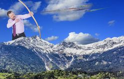 Businessman practicing archery with mountain Stock Image