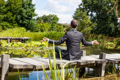 Businessman practicing meditation on wooden path above water Royalty Free Stock Photography