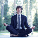 Businessman practicing yoga. Businessman in suit practicing yoga in park royalty free stock photo