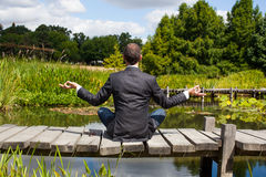Businessman practicing yoga on wooden path above water Stock Photo