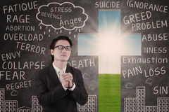 Businessman praying on chalkboard and cross background Royalty Free Stock Image