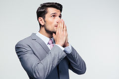Businessman praying over gray background Stock Image