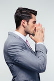 Businessman praying over gray background Royalty Free Stock Images