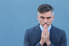 Businessman praying. Thoughtful mature man in formalwear holding hands clasped near face and while standing against blue wall Stock Image