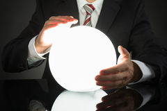 Businessman Predicting Future With Crystal Ball. Close-up Of Businessman Predicting Future With Crystal Ball At Desk royalty free stock images