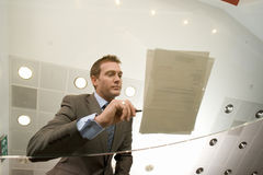 Businessman preparing to sign paperwork on glass table, low angle view through glass Stock Photos