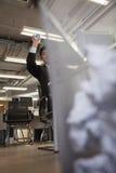 Businessman preparing to throw paper into wastebasket Stock Image