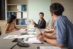 Businessman present financial chart with team in the meeting Stock Image