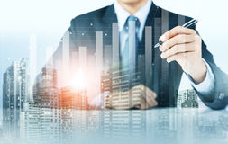 Businessman present increasing graph with city background Stock Photos