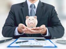 Businessman present pink piggy ceramic bank on hand stock photography