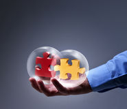 Businessman presenting a brand new solution. Two puzzle pieces in glass spheres Stock Photo