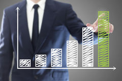 Businessman presenting a chart. Businessman presenting a successful sustainable development on a bar chart Royalty Free Stock Photos