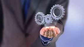 Businessman presenting cogs and wheels graphic stock video
