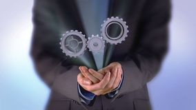Businessman presenting cogs and wheels graphic stock footage