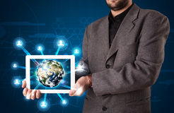 Businessman presenting 3d earth globe in tablet Stock Images
