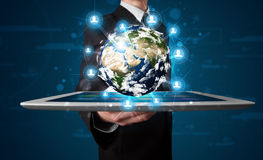 Businessman presenting 3d earth globe in tablet Stock Image