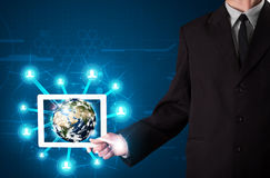 Businessman presenting 3d earth globe in tablet Stock Photography