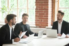 Businessman presenting document to investors, negotiating with p. Businessman in suit presenting documents to investors at meeting, men talking convincing royalty free stock photo