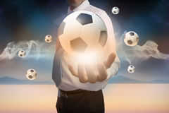 Businessman presenting floating footballs Stock Images