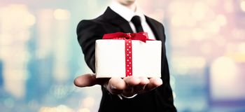 Businessman presenting a gift box Royalty Free Stock Photography