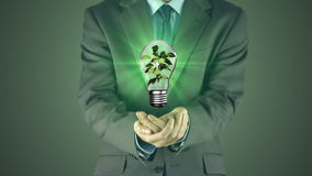 Businessman presenting light bulb with hands stock footage