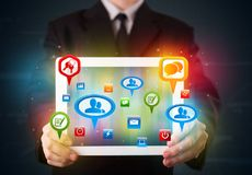 Businessman presenting modern tablet with colorful social signs and icons. Young businessman presenting modern tablet with colorful social signs and icons Royalty Free Stock Image