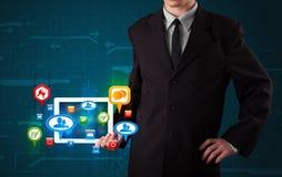 Businessman presenting modern tablet with colorful social signs. Young businessman presenting modern tablet with colorful social signs and icons stock illustration