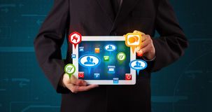 Businessman presenting modern tablet with colorful social signs Royalty Free Stock Images