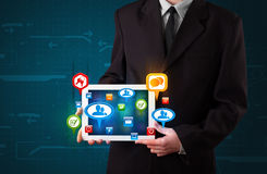 Businessman presenting modern tablet with colorful social signs Royalty Free Stock Photos