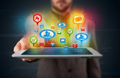 Businessman presenting modern tablet with colorful social signs Stock Image