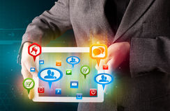 Businessman presenting modern tablet with colorful social signs. Young businessman presenting modern tablet with colorful social signs and icons vector illustration
