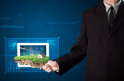 Businessman presenting a perfect ecology land with a house and w Stock Photo