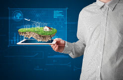 Businessman presenting a perfect ecology land with a house and w Royalty Free Stock Photos