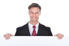 Businessman Presenting Placard. Portrait Of Mature Businessman Presenting Blank Placard Royalty Free Stock Images