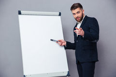 Businessman presenting something on blank board. Portrait of a confident businessman presenting something on blank board over gray background royalty free stock image
