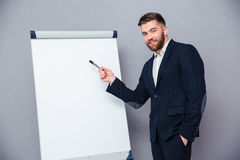 Businessman presenting something on blank board. Portrait of a happy businessman presenting something on blank board over gray background stock image