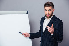 Businessman presenting something on blank board. Portrait of a young businessman in suit presenting something on blank board over gray background stock photography