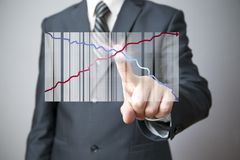 Businessman presenting a successful sustainable development. Business concept. Businessman presenting a successful sustainable development on a bar chart on gray Stock Photo